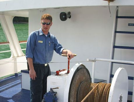 A male professional mariner pulls up the ship anchor