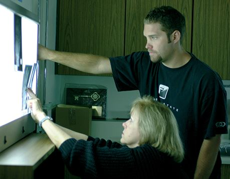 A student standing next to an instructor views an x-ray displayed on a film illuminator