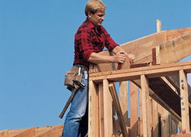 Man in plaid shirt stands on a roof frame