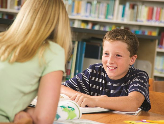 Speech-Language Pathology Assistant sits across from a smiling boy in a library