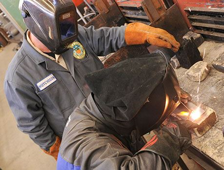 Two welders in welding gear work in welding lab