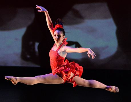 Female dancer in red costume performs a grand jete