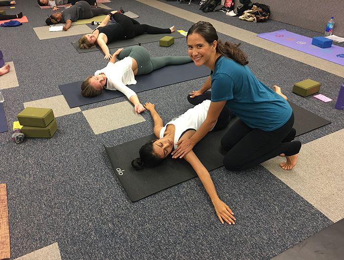 Female yoga instructor smiles at camera as she corrects form of student