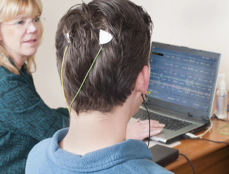 A male sits with electrodes attached to back of head and a screen showing his brain activity