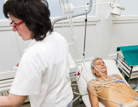 A cardiovascular technician stands near a patient who has been prepped with electrodes for an EKG