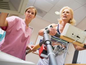 Electrocardiography technician reviews patient's results while patient walks on treadmill