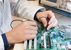 A man works with a soldering iron on a motherboard