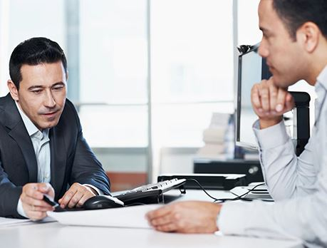 Man in business suit reviews report with another person while sitting at a conference table