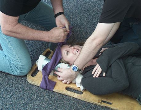 Two male EMTs secure female patient on spineboard