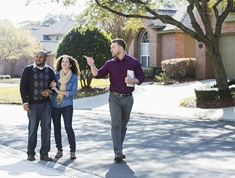 Rea estate salesman tours a neighorhood with a couple