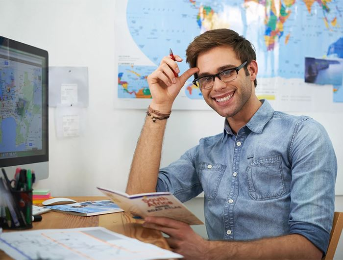 Male travel specialist sits at desk holding a travel brochure and smiling at camera