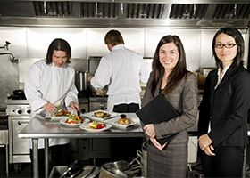 Two women in business suits smile at camera amidst a kitchen where food is being plated