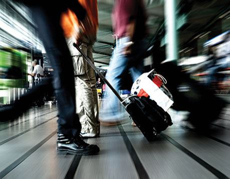 Blurred image of people walking at an airport and their suitcases