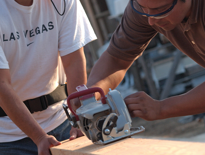 Two men use table saw to cut wood planks