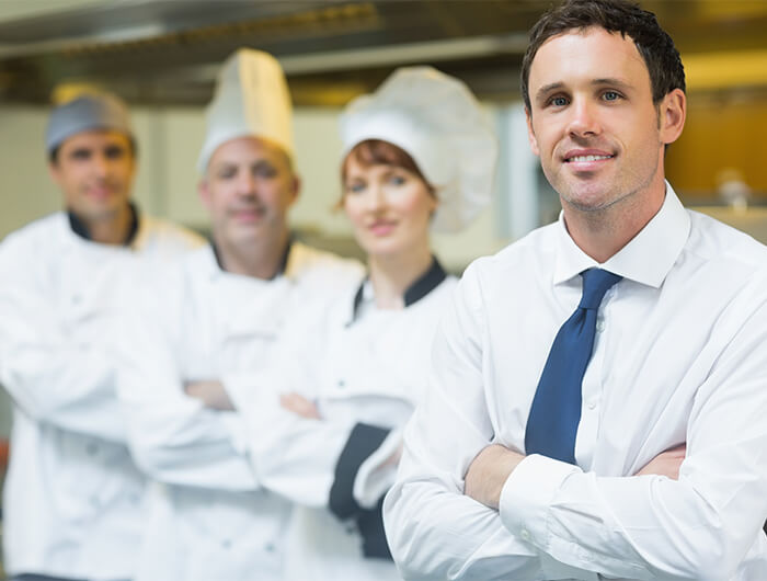 Male restaurant manager poses with chefs in background