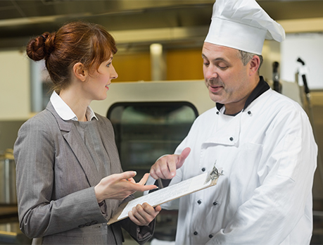 Female restaurant manager consults with male cook in a commercial kitchen