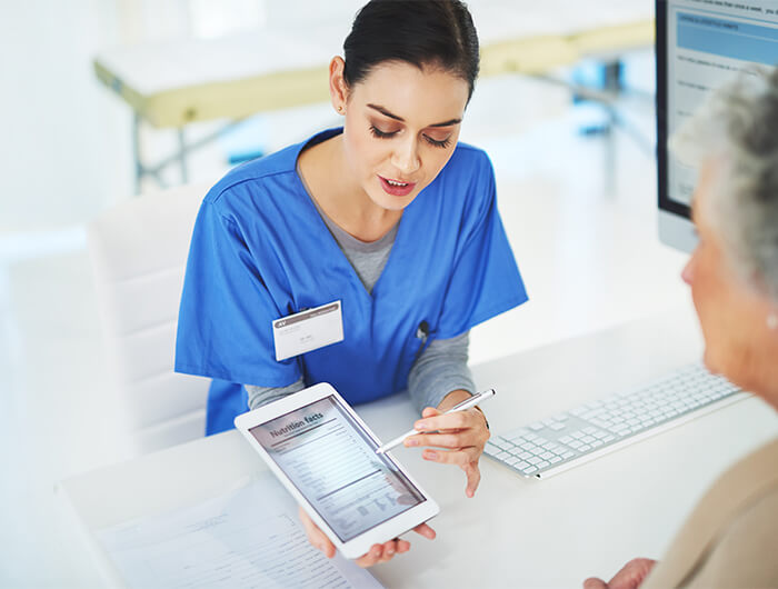 Female nutritional technician shows a patient information on a tablet