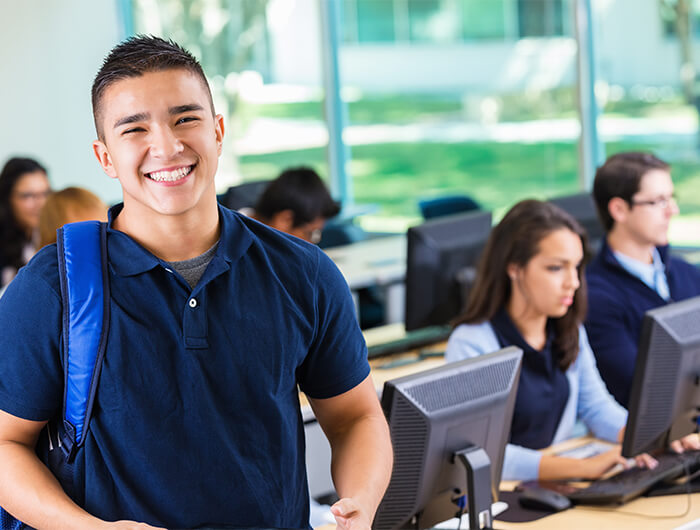 Male high school student smiling in computer lab