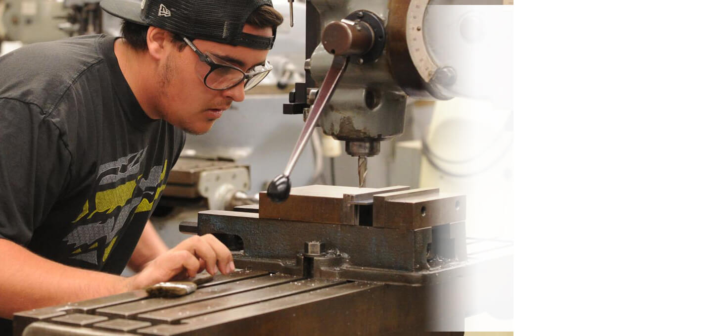 College Student using a drill press
