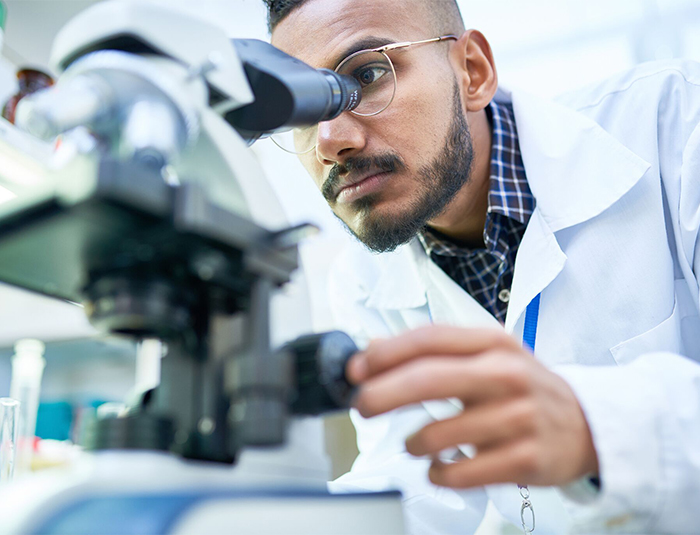 man with glasses and lab coat peering into microscope
