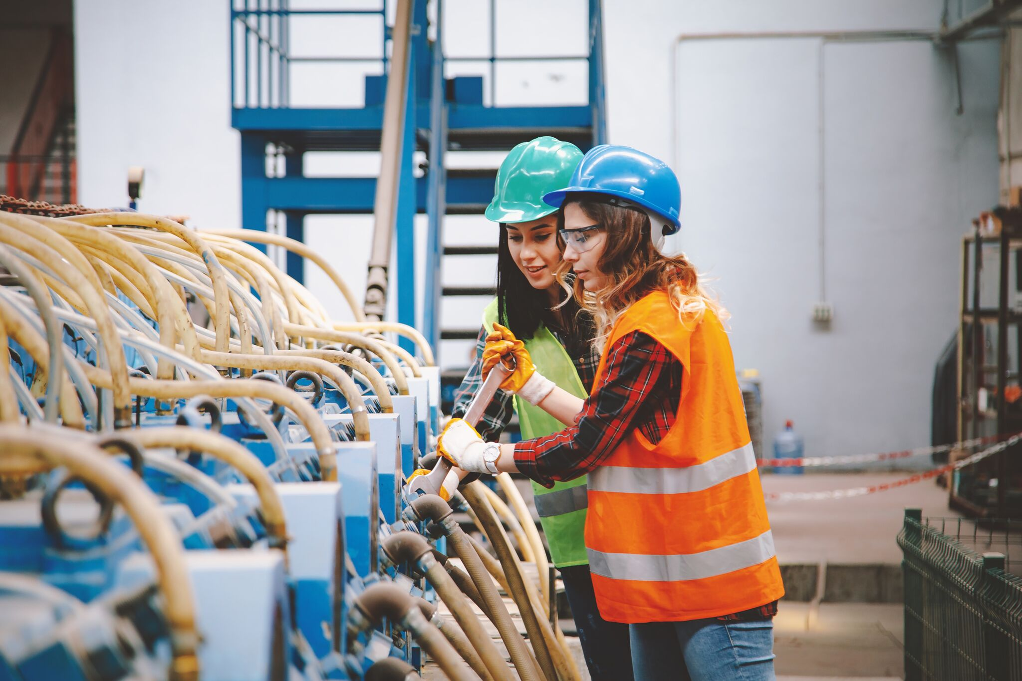 two young women wearing safety gear working on automation equipment