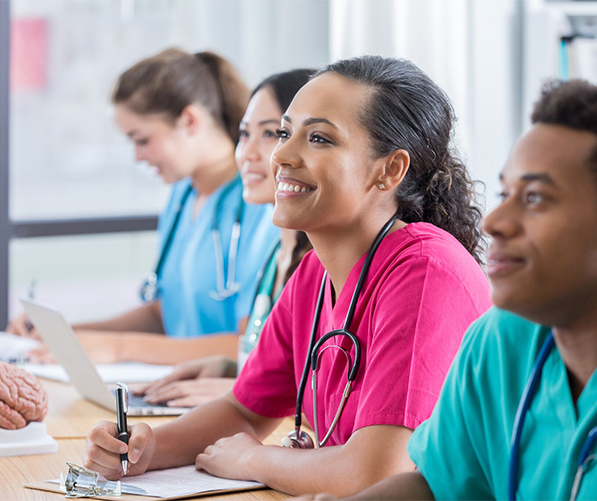 health care students in a classroom, wearing scrubs and smiling