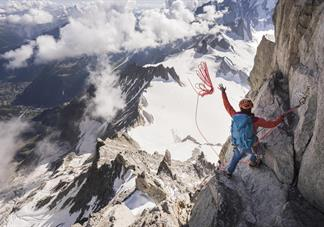 banff promotional image showing mountain climber on steep mountainside throwing rope