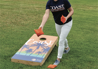 photo of woman throwing orange beanbags with Coast themed cornhole board in background