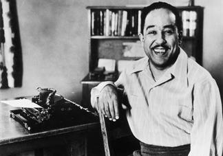 black and white photograph of langston hughes sitting in front of typewriter