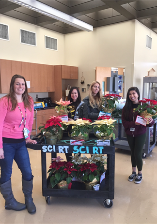 photo of volunteers pushing cart to deliver poinsettias