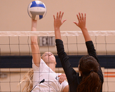 OCC Women's volley player jumps up for the ball