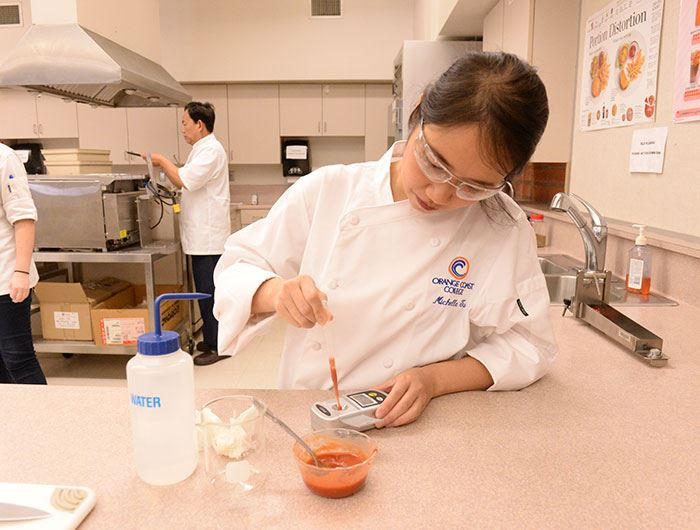 Culinology assistant tests a red sauce with an instrument