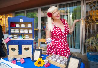 OCC alum jenna davis posing with her sunscreen product in a red and white polka dot dress